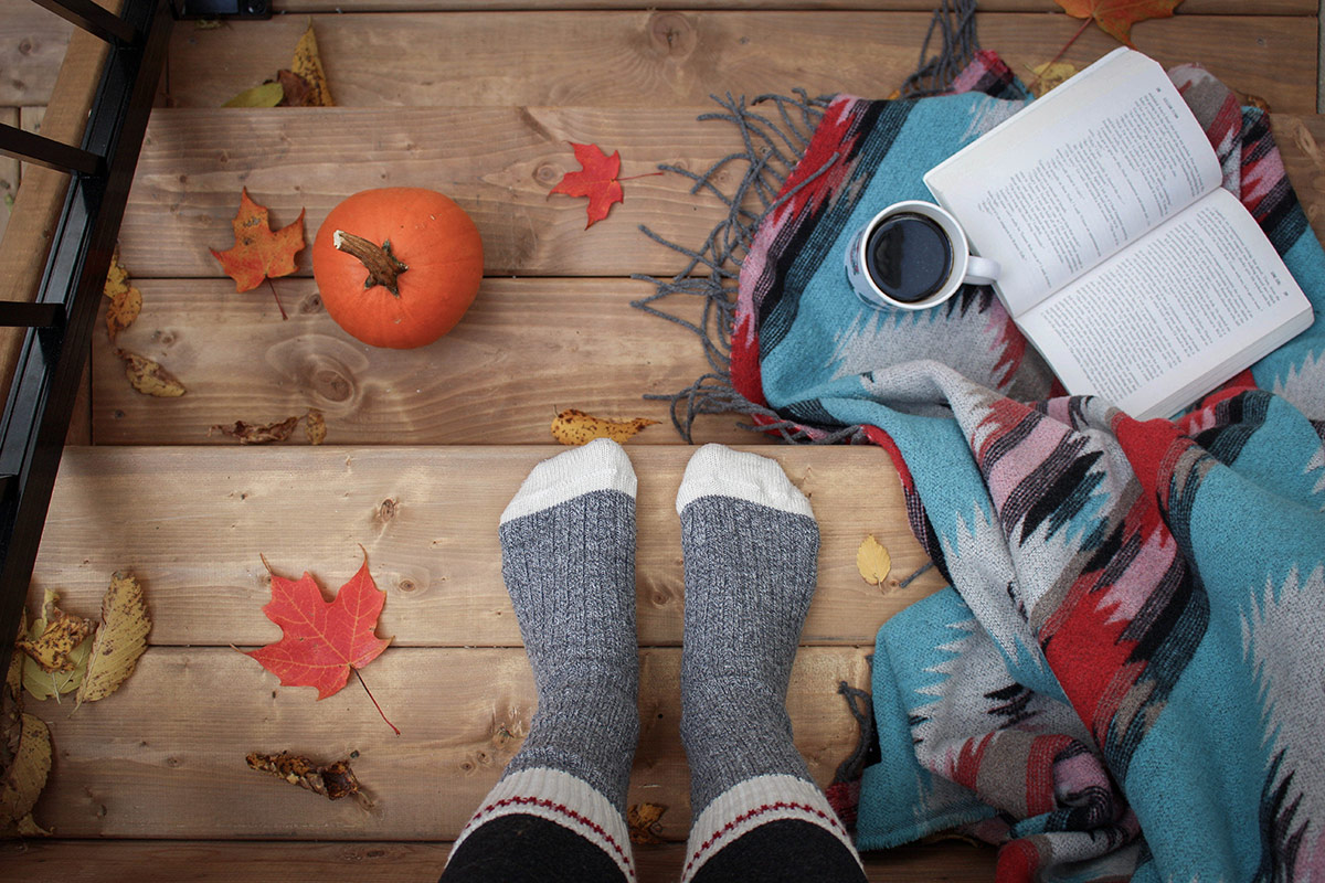 collection of autumnal items including warm thick socks a cup of coffee and a small pumkin