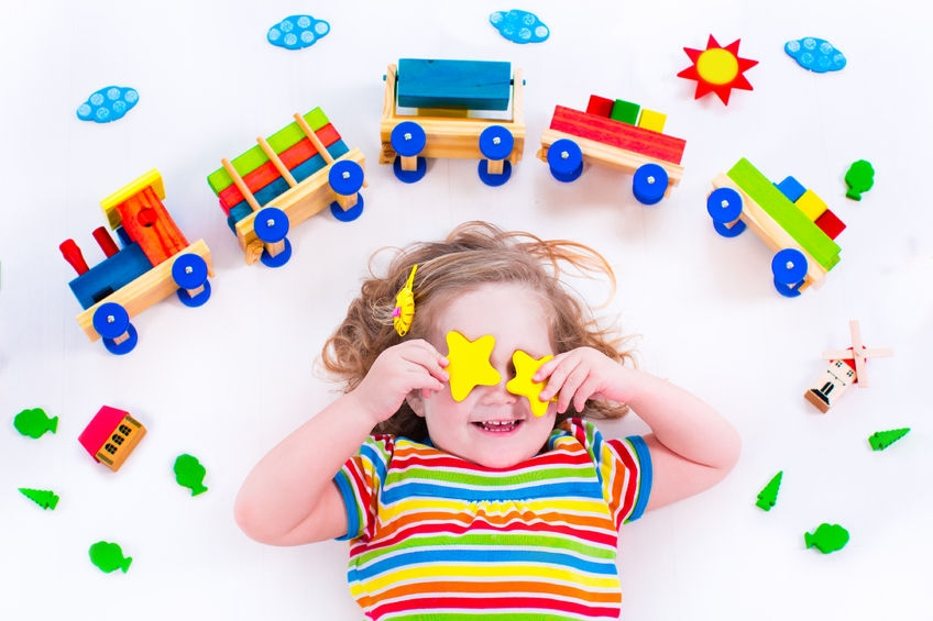 young girl with lots of toys surrounding her
