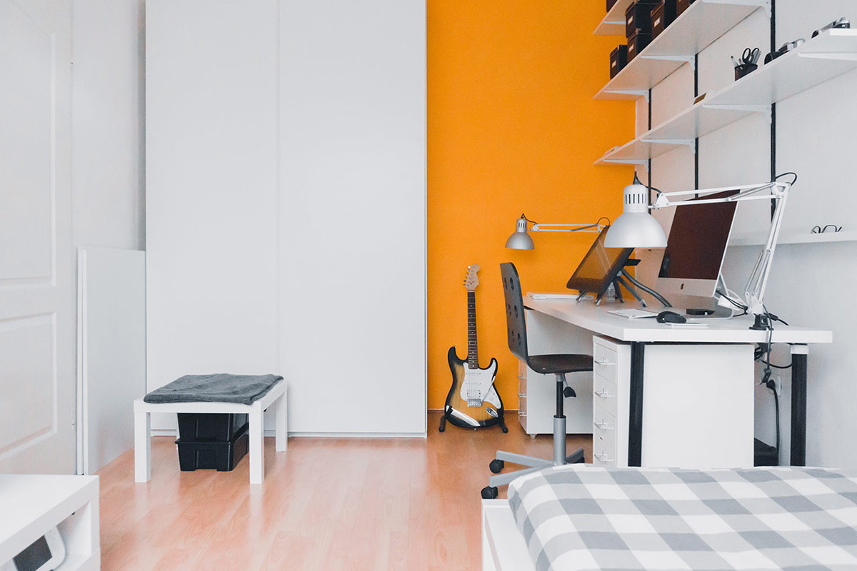stunning orange and white small studio with lots of shelving and personal items
