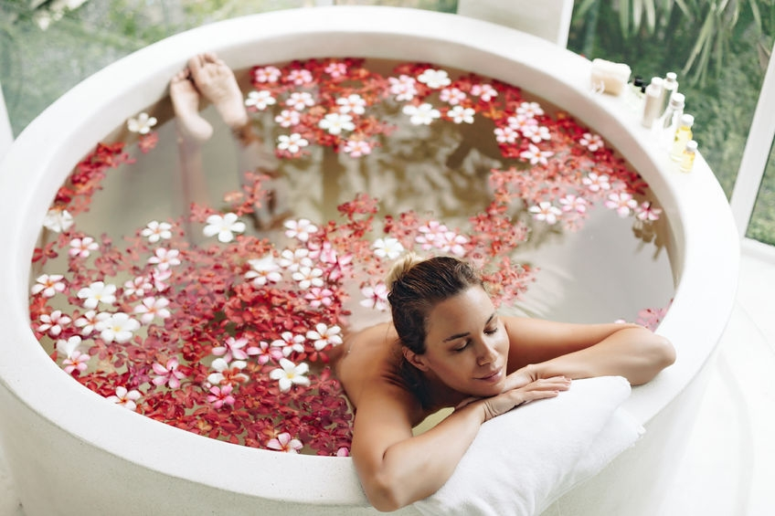 woman laying in circular bath filled with warm water and rose petals