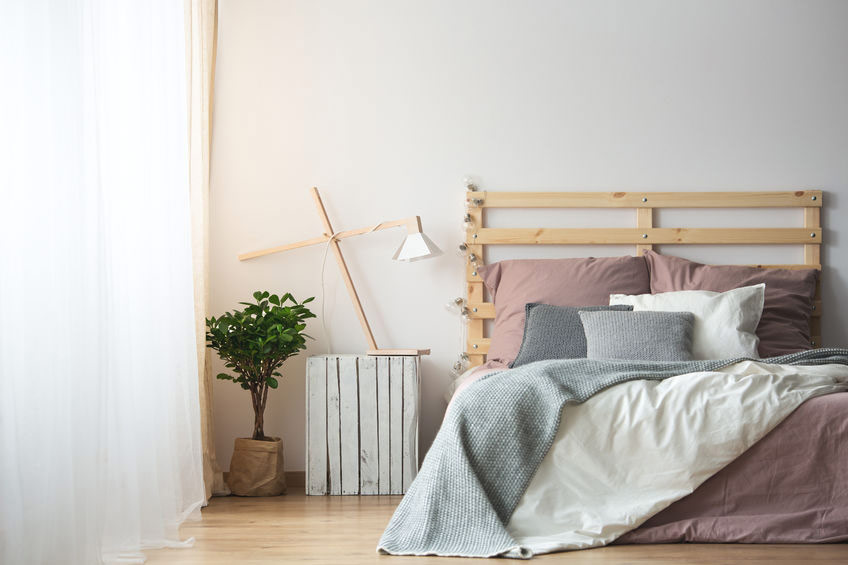 stunning and simple bedroom with wooden accessories and a blush pink duvet set
