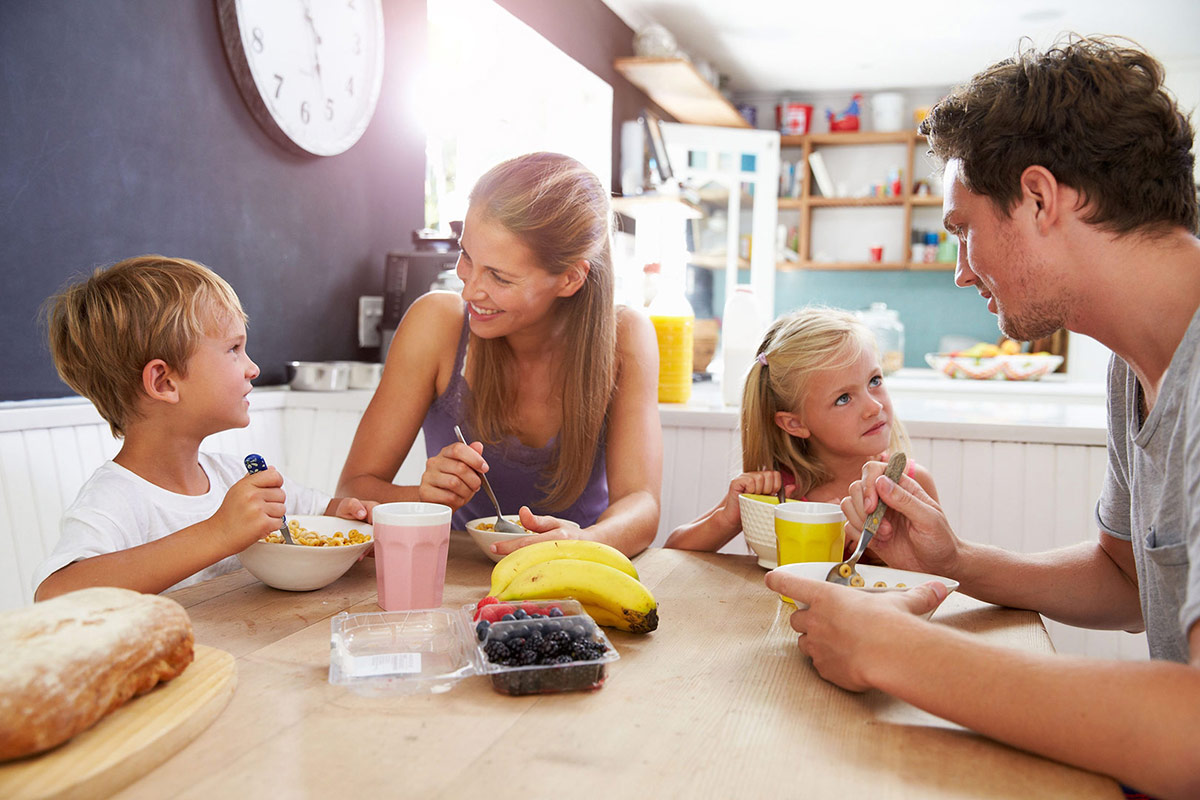 young happy family sitting around a dining table for breakfast