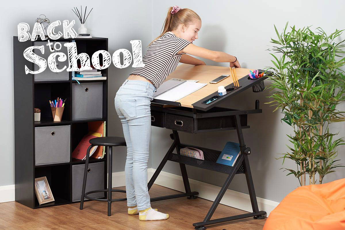 young girl adjusting her drawing table in her work station