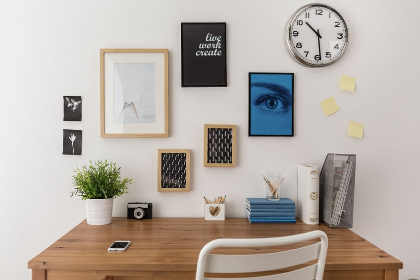 neat home office with lots of reminders on the wall and photo frames