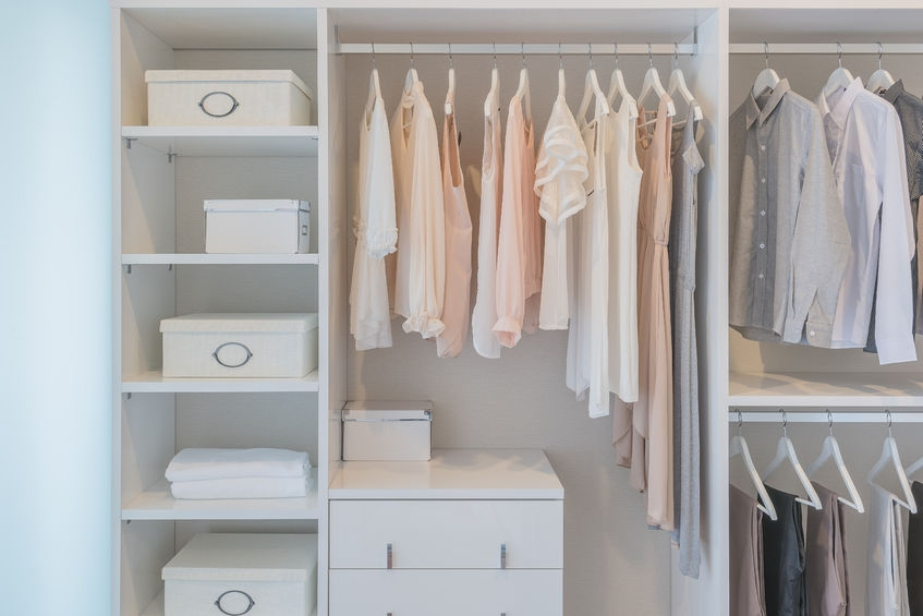 super organised cupboard with light pink and white clothing hung up and storage boxes