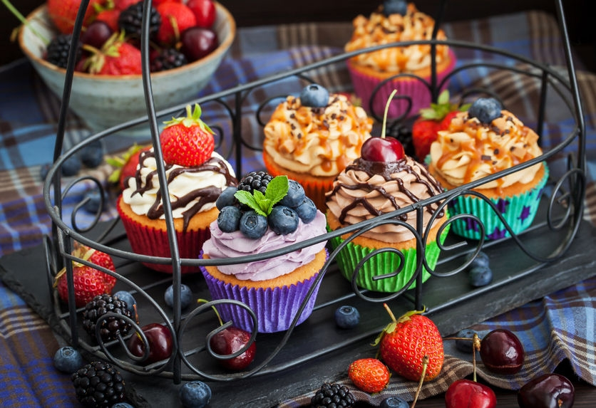 stunning and colourful cupcakes in a wire basket with gorgeous decorations and lots of icing