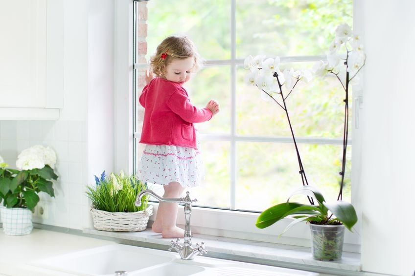 beautiful white room with lots of plants and a little girl looking out of the window