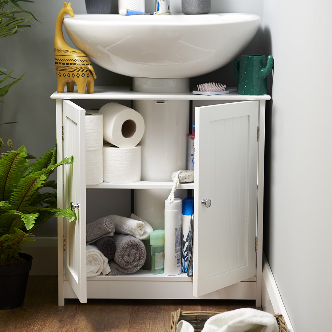 white under sink cabinet in a natural bathroom with lots of beauty essentials in the cupboard