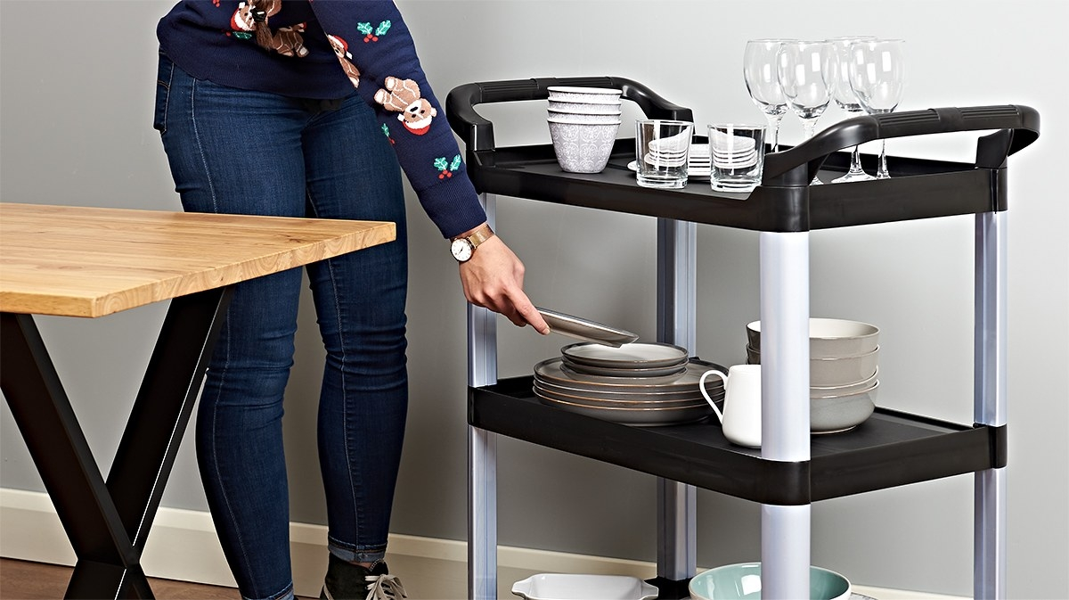 black and silver serving trolley with lots of crockery and wine glasses on being used by a woman
