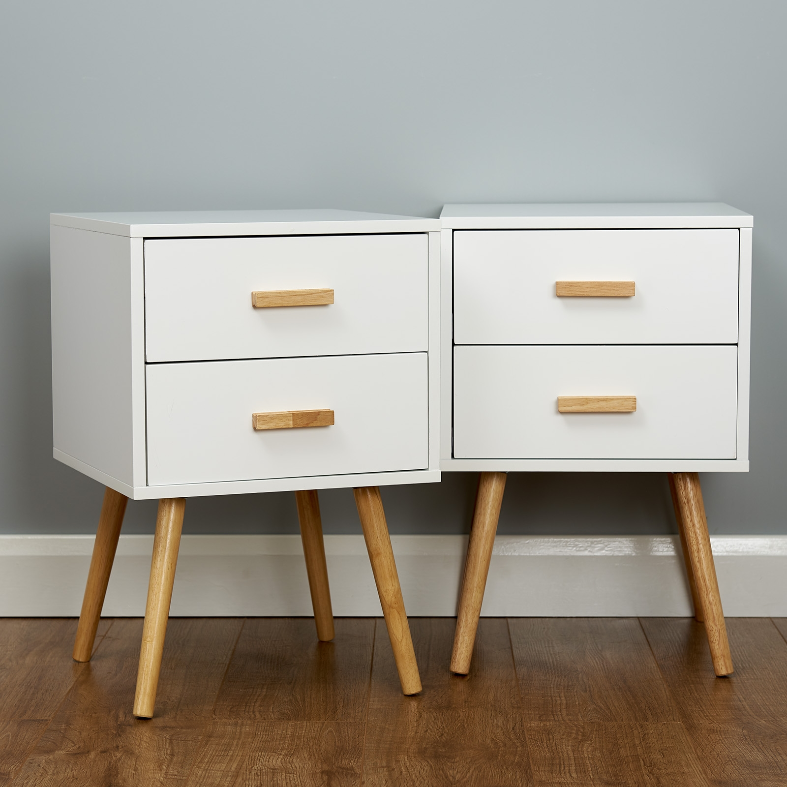two white retro bedside tables stood together in a grey painted room with wooden flooring