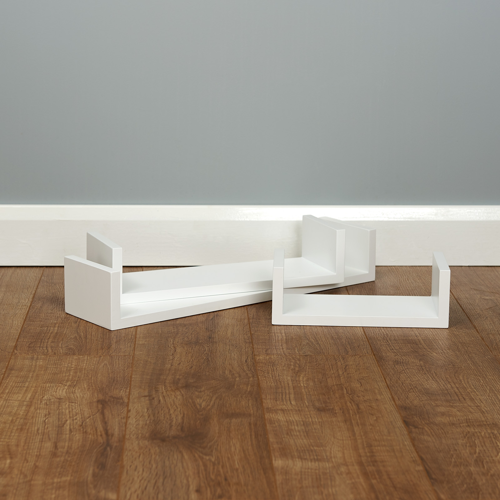 stunning modern white floating shelves on a wooden floor in a grey painted room