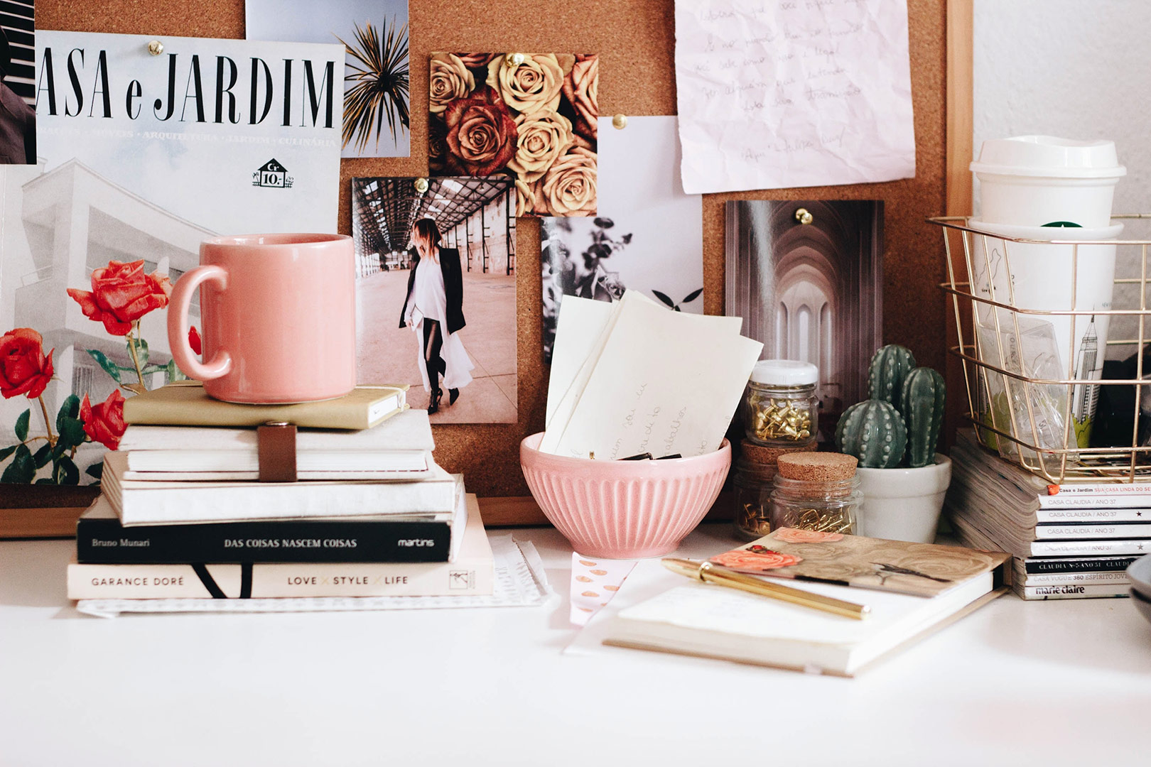 cute little desk area with lots of personal items on like coffee mugs and notepads