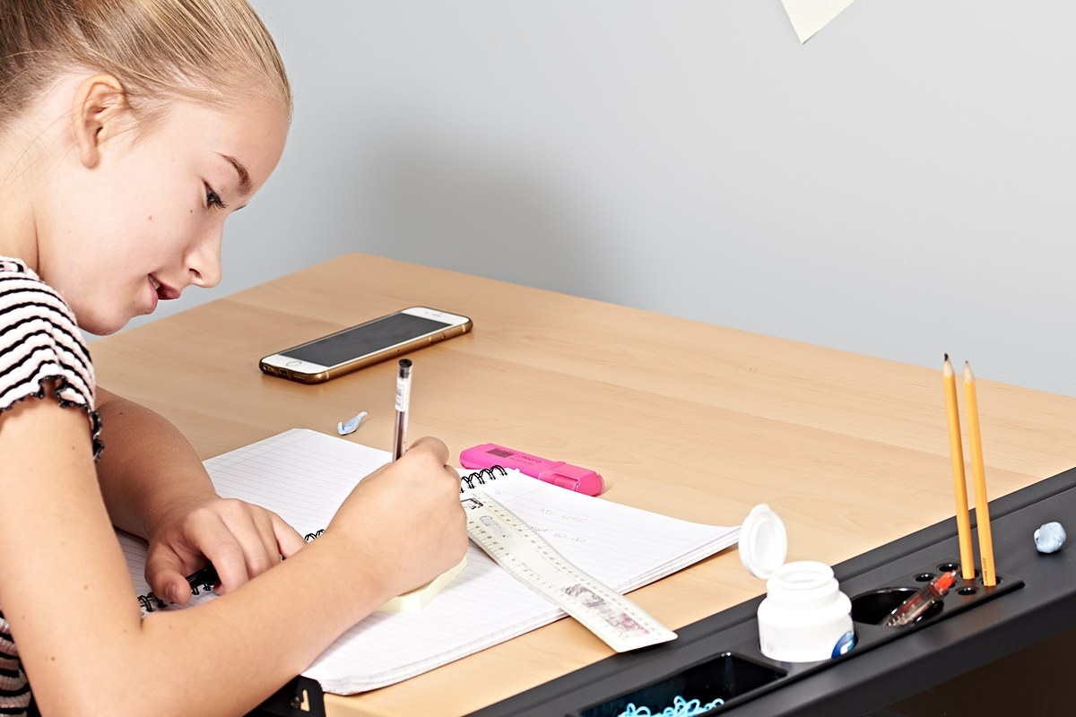 young woman using the wooden drawing table to do work at