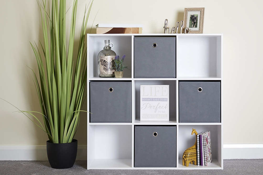 stunning white cube unit with grey storage boxes and a beautiful plant in a living room