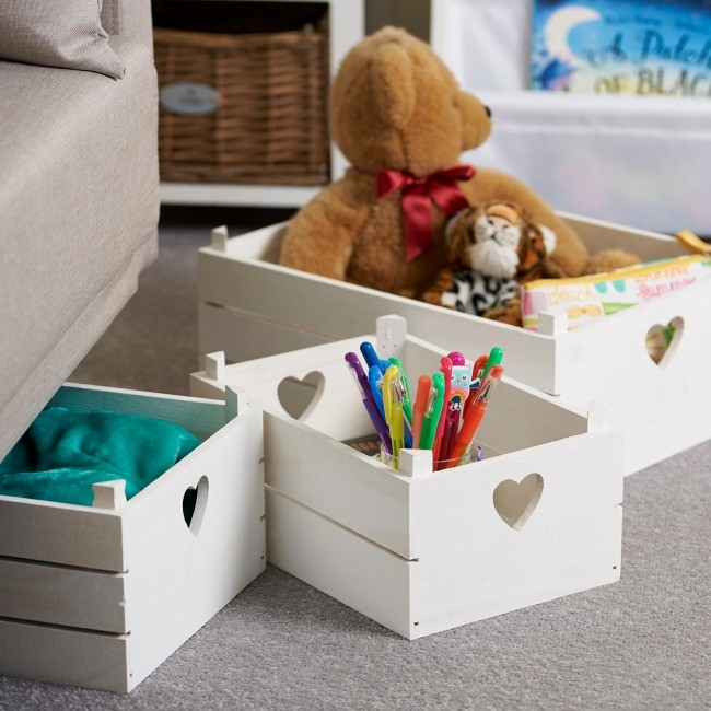 white storage crates with heart handles and childrens toys inside