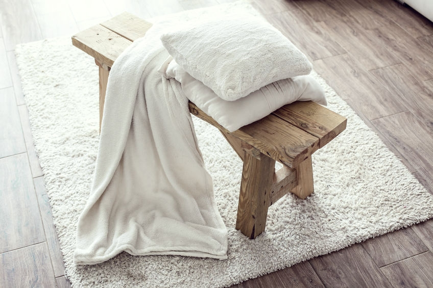 cute wooden bench with fresh white linen on top