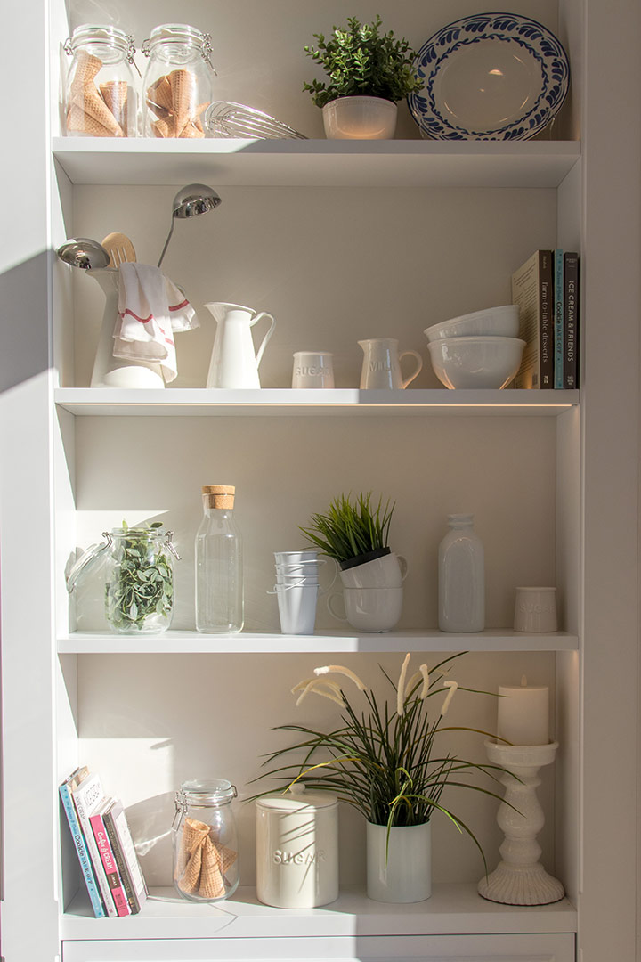 stunning white shelving being used as a pantry with lots of kitchenware and food