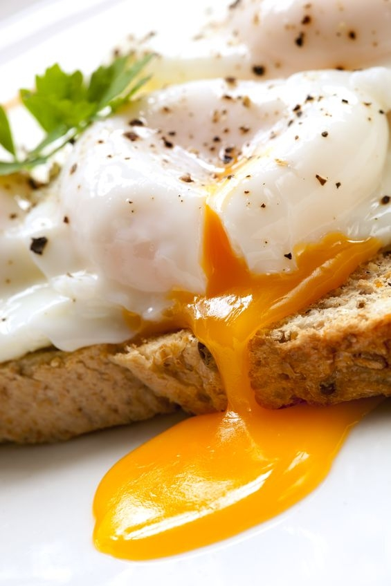 gooey poached egg on toast with yolk drizzling out of centre