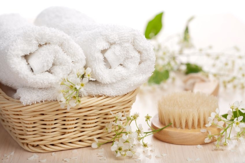 gorgeous white fluffy towels in wicker basket with foliage