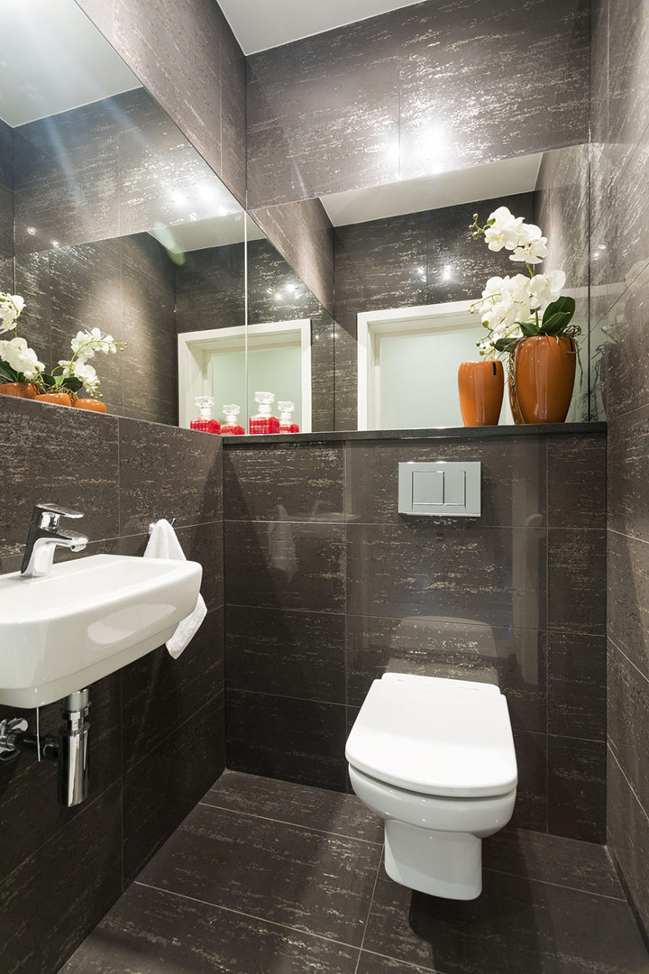small-bathroom-with-dark-tiled-walls-orange-vase-with-plant-and-white-modern-toilet-and-sink