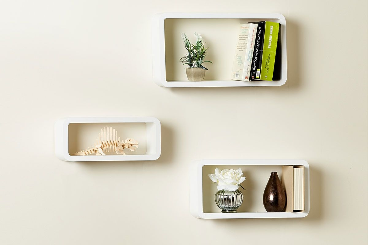 three white curved rectangle floating shelves with ornaments and plants displayed on