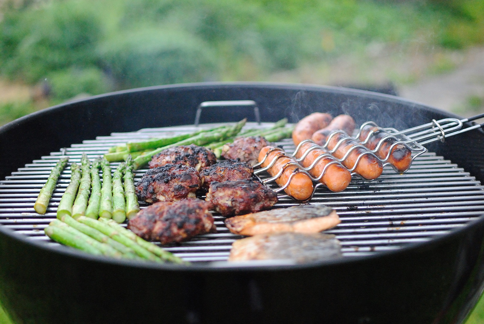sausages burgers and asparagus on a barbecue