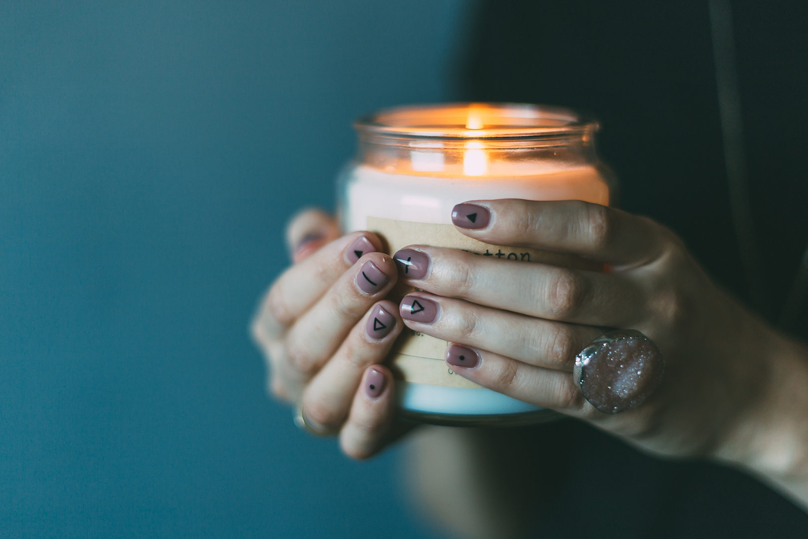 woman hands holding a lit candle