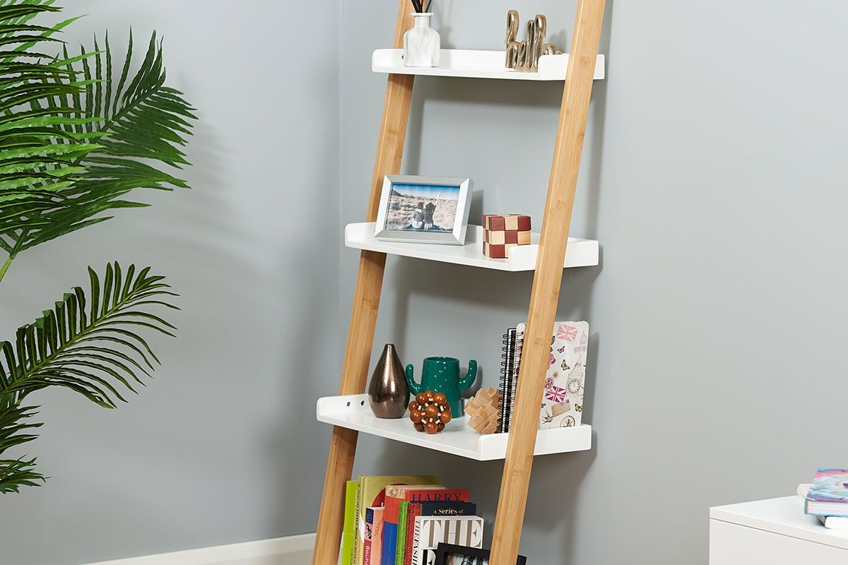 white and bamboo ladder shelf from hartleys direct leaning against a grey wall in a bedroom set up