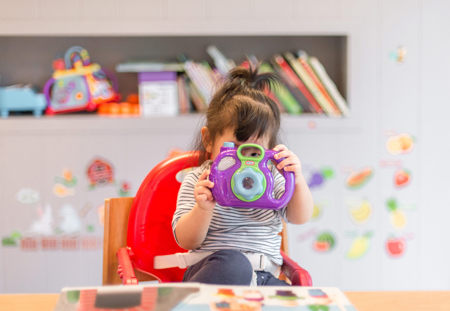 young brunette girl olding a plastic camera up to her face in playroom