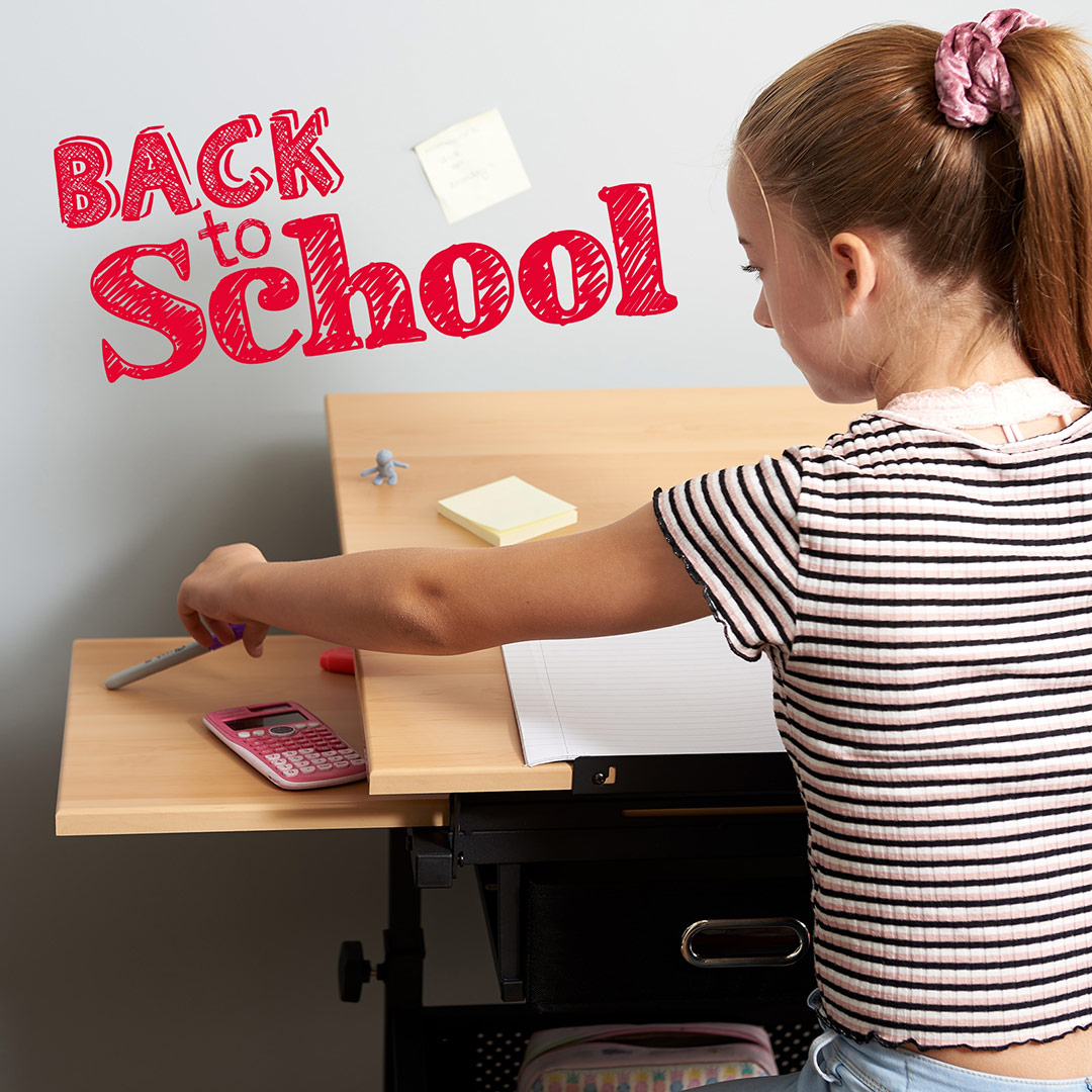 young girl using a wooden drawing table for her homework