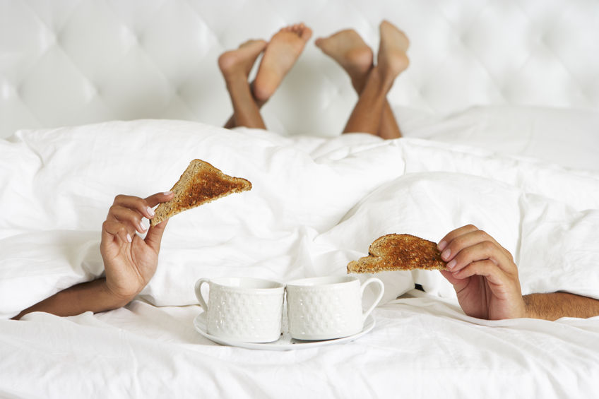 Couple under the duvet eating toast