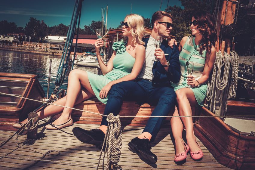 Man with beautiful women drinking champagne on a boat
