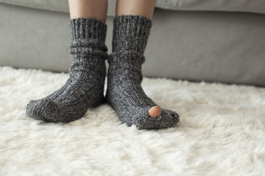Feet in socks with a hole on a rug